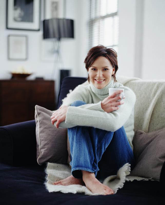 Woman sitting on couch drinking coffee after Individual Counseling session