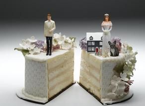 wedding cake cut in half with bride and groom on either side